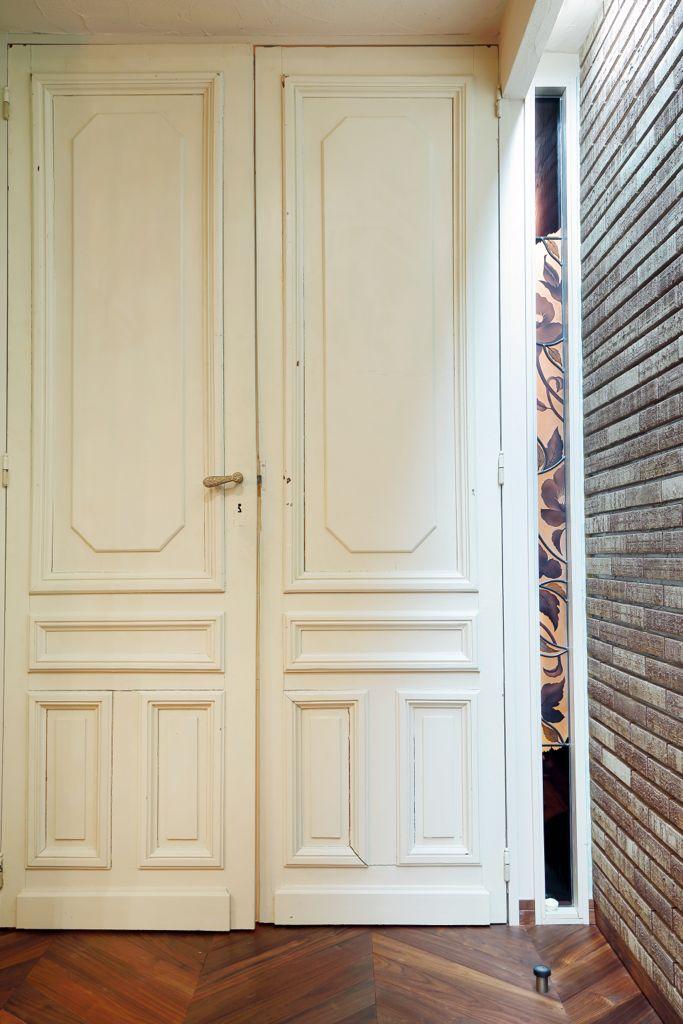 ソファの色に合わせて特注したステンドグラス。リビングドアはアンティークの一点もの。どちらにもM様のこだわりがにじむ。