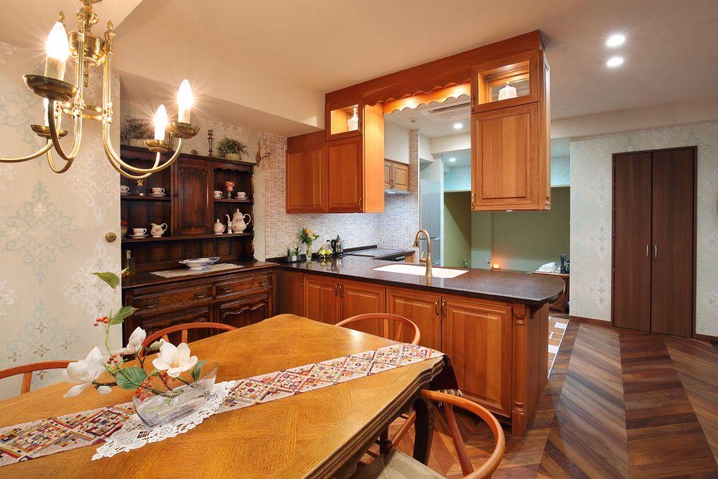 アンティークのサイドボードとダイニングテーブル。重厚感と存在感では、真新しいキッチンもまったく負けていない。キャビネットのこちら側についている扉は、一面が浅い食器棚になっていて、ほぼすべての食器が収納されている。