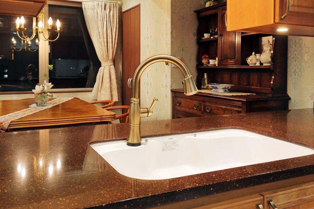 ずっしりした重量感があるタッチ水栓。木製のキッチンキャビネットや独特な色合いの天板とも見事にマッチし、品格と輝きを添えている。実用的ながら生活感がないのが魅力。