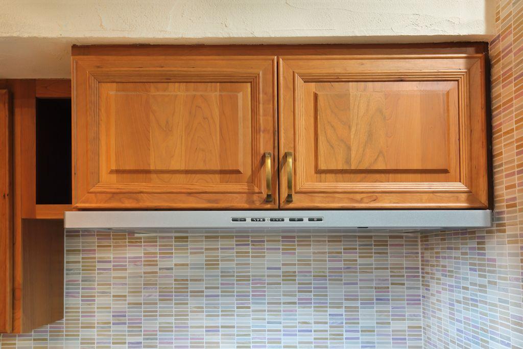 通常はステンレス製が多いレンジフード。しかし、キッチンキャビネットに合わせて高級感のある木製の扉をつけた。