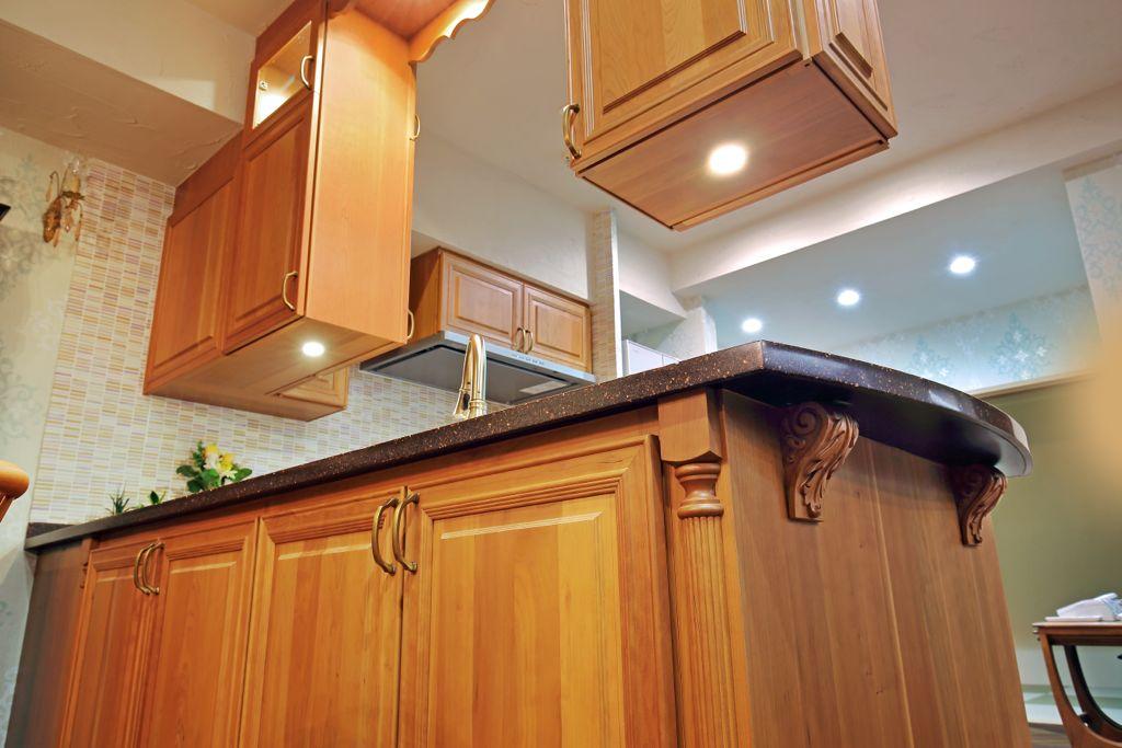 つり戸棚下の照明から天板に光が美しく反射する。天板下に装飾を添えてインテリア性を高めたのは、DeWilsデザイナーのこだわり。