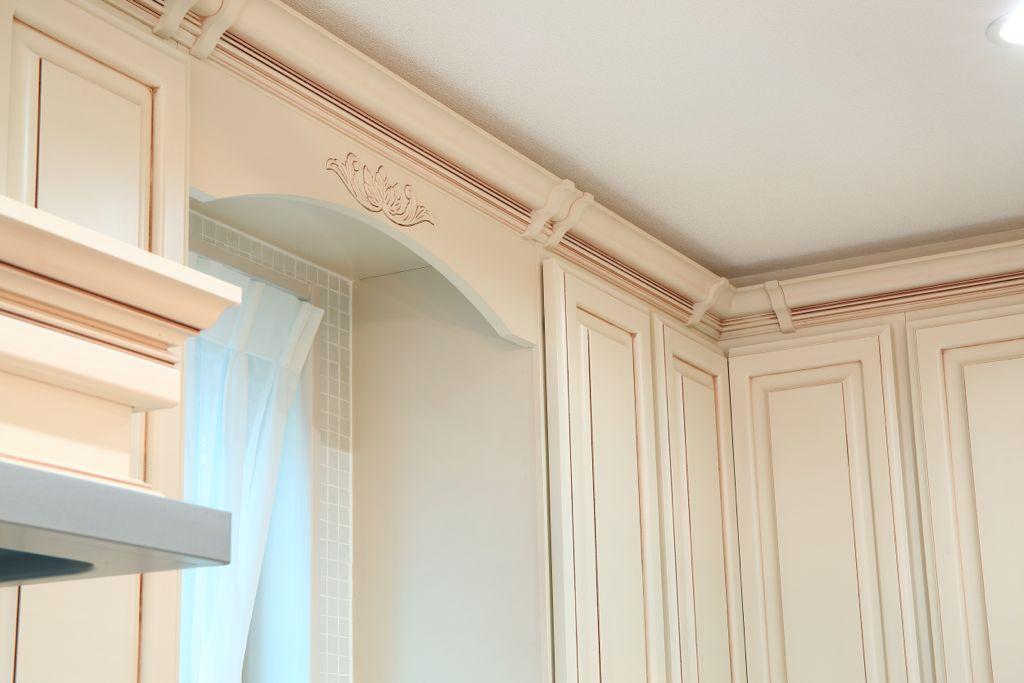 キャビネットと天井の境に巡らされたモールディングと呼ばれる飾り。ところどころ縦に飾りが⼊った独特のデザインは⽇本では珍しいスタイル。⾼級感が増すと同時にアメリカン・キッチンらしい雰囲気になっている。