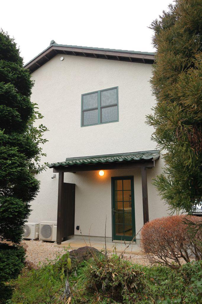 白っぽい壁の四角い家に、瓦の屋根。四角い窓に、大きめの軒がついた、オーソドックスな外観。