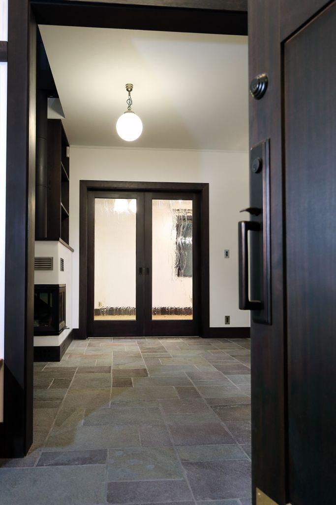 内開きの玄関ドアを開けて室内を臨むと、シンプルな白い漆喰の壁と黒っぽい木がメインとなったシンプルな部屋が広がっています。