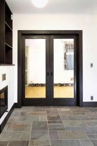 石のタイルと、どっしりとした構えのダイニングキッチンへと続くガラス扉は 大正〜昭和初期の家を思わせます。